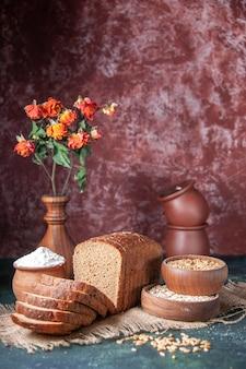Vista verticale di pane nero fette di farina in una ciotola e farina d'avena cruda di grano su asciugamano di colore nudo e vasi di fiori su sfondo di colori misti