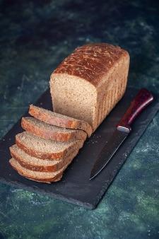 Vista verticale del coltello a fette di pane nero su tavola di colore scuro su sfondo in difficoltà di colori misti