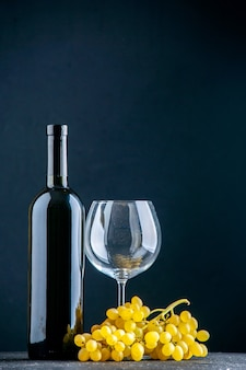 Vertical view of a bundle of yellow grape and bottle glass goblet on dark background