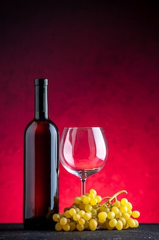 Vertical view of a bundle of yellow grape and bottle glass goblet on red background
