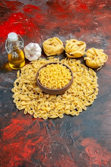 Vertical view of butterfly uncooked pastas in a brown bowl spaggeti garlic and oil bottle on mixed color background