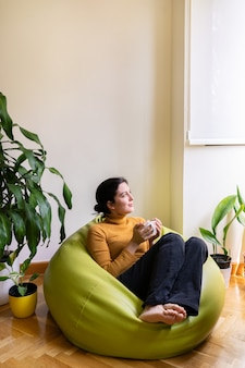 Vertical view of casual woman at home drinking herbal tea sit on a green pouf.