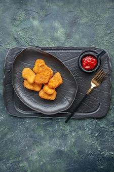 Vista verticale di pepite di pollo su un piatto nero e forchetta ketchup sul vassoio di colore scuro su superficie scura