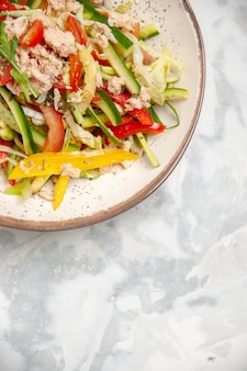 Vista verticale di insalata di pollo con verdure su superficie bianca macchiata