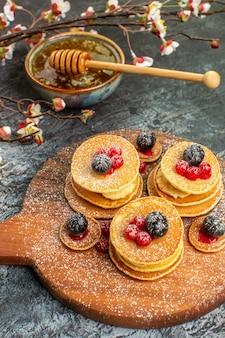 Vista verticale del miele delle frittelle americane classiche in una ciotola su gray