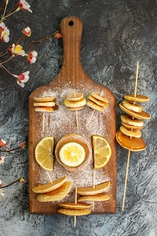 Vertical view of classic american pancakes with lemons on wooden cutting board on gray