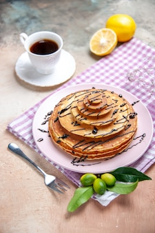 Vertical view of classic delicious pancakes decorated with chocolate syrop on pink stripped towel
