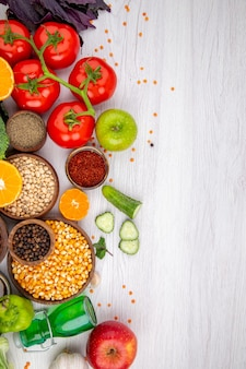 Vertical view of collection of fresh foods and spices vegetables on white table