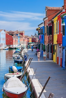Vertical view of colorful street with canal in burano, near venice, italy