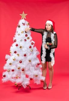 Vista verticale della giovane donna confusa in un vestito nero con il cappello di babbo natale e che decora l'albero del nuovo anno sul rosso