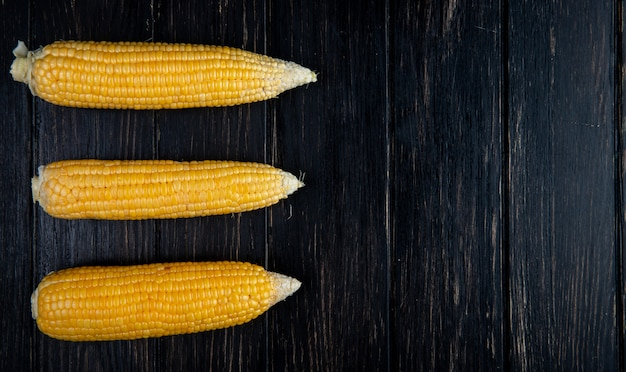Vertical view of cooked corns on left side and black table