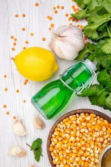 Vista verticale dei chicchi di mais caduto olio bottiglia aglio limone verde sul tavolo bianco