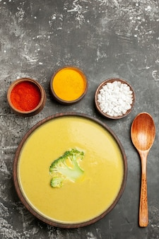 Vertical view of creamy broccoli soup in a brown bowl different spices and spoon on gray table