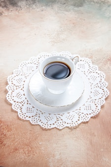 Vista verticale di una tazza di tè nero sul tovagliolo decorato bianco su colorato