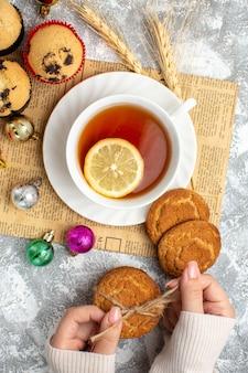 Vista verticale di una tazza di tè nero con limone e accessori decorativi su un vecchio biscotto di giornale e piccoli cupcakes sulla superficie del ghiaccio