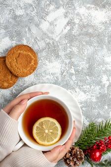 Vista verticale di una tazza di tè nero con rami di limone e abete con cono di conifere sulla superficie del ghiaccio