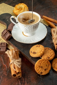 Vertical view of cup of coffee on wooden cutting board cookies cinnamon limes chocolate bars on dark background
