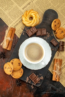 Vertical view of cup of coffee on wooden cutting board on an old newspaper cookies cinnamon limes chocolate bars on dark background