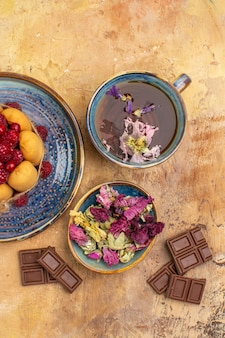 Vertical view of a cup of hot herbal tea soft cake with fruits and flowers chocolate bars