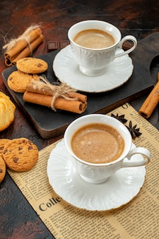 Vertical view of cups of coffee on wooden cutting board and an old newspaper cookies cinnamon limes chocolate bars on dark background