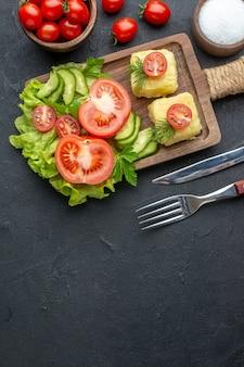 La vista verticale del formaggio dei cetrioli e dei pomodori freschi tagliati sulle posate del bordo di legno ha messo il sale sulla superficie nera