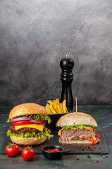 Vista verticale di interi gustosi panini tagliati e pomodori con gambo sul vassoio nero sulla superficie di colore scuro della miscela