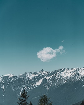 Vertical view of a cute small cloud with the background of mountains and blue sky