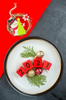 Vertical view of decoration accessories numbers on a plate on a dark table