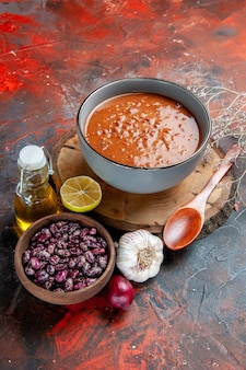 Vertical view of deliciou soup for dinner with a spoon and lemon on a wooden tray beans garlic onion and oil bottle on mixed color background
