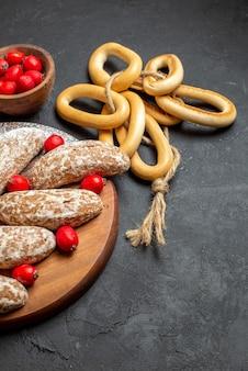 Vista verticale di deliziosi biscotti alla banana con frutta sul vassoio di legno marrone sulla tavola nera