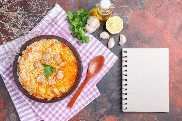 Vista verticale di deliziosa zuppa di pollo con noodles verdi e cucchiaio su rosa asciugamano spogliato bottiglia di olio aglio limone e taccuino su sfondo scuro