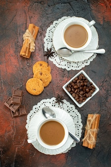 Vertical view of delicious coffee in white cups cookies cinnamon limes chocolate bars on mixed color background