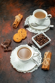 Vertical view of delicious coffee in white cups on napkins cookies cinnamon limes chocolate bars on mixed color background