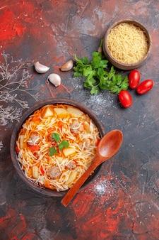Vista verticale di deliziosa zuppa di noodle con pollo e pasta cruda in una piccola ciotola marrone e cucchiaio di pomodori e verdure all'aglio sullo sfondo scuro