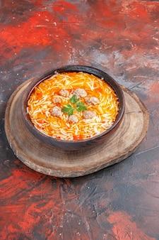 Vista verticale di deliziosa zuppa di noodle con pollo su tagliere di legno su sfondo scuro