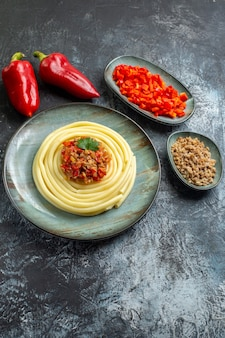 Vertical view of delicious pasta meal on a blue plate served with tomato and meat for dinner and its ingredients
