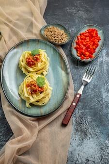 Vista verticale di un delizioso pasto di pasta su un piatto blu servito con pomodoro e carne per cena su un asciugamano color marrone chiaro i suoi ingredienti