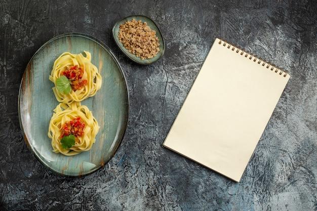 Vista verticale di una deliziosa pasta con carne di pomodoro e verde su un piatto blu accanto a un quaderno a spirale su sfondo di ghiaccio