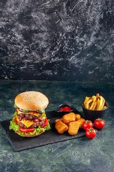 Vista verticale del delizioso panino e ketchup di pepite di pollo sui pomodori vassoio di colore scuro sulla superficie nera