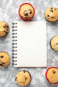 Vertical view of delicious small cupcakes with chocolate around closed notebook on ice surface