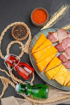 Vista verticale di deliziosi snack bottiglie cadute peperoni su asciugamano e corda su sfondo nero