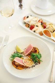 Vertical view of a delicious tuna dish with a glass of wine and a cheese set