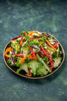 Vista verticale di deliziosa insalata vegana in un piatto con varie verdure fresche su sfondo scuro