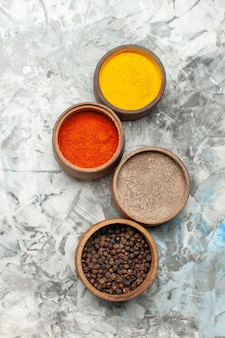 Vertical view of different spices in brown bowls on gray background