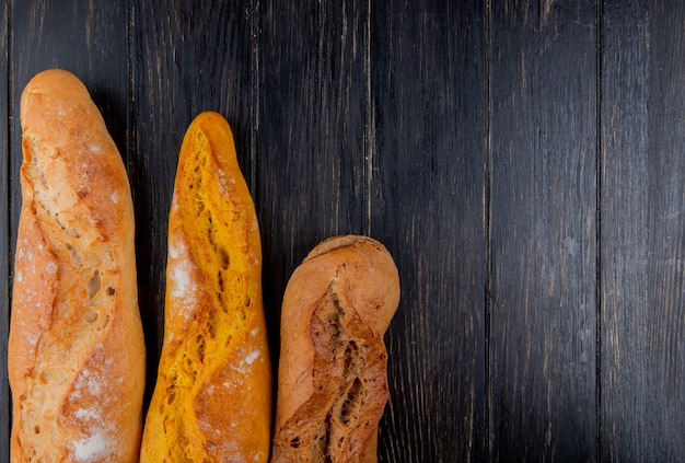 Vertical view of different types of baguette on wooden background with copy space