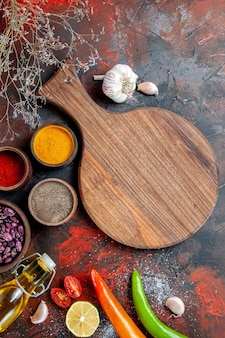 Vertical view of dinner background fallen oil bottle beans cutting board and different spices