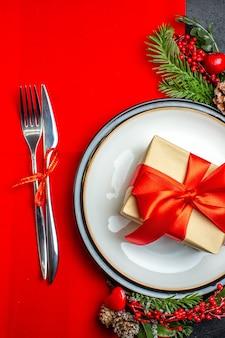 Vista verticale di piatti piani con regalo su di esso e rami di abete posate set accessorio decorazione cono di conifera su un tovagliolo rosso