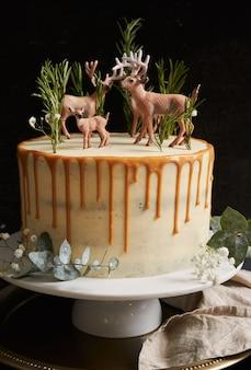 Vista verticale di una torta da sogno con crema bianca e gocce d'arancia con una foresta e renne in cima