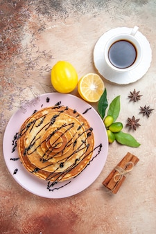 Vertical view of easy pancakes decorated with chocolate syrup with lemonnd tea on colourful table