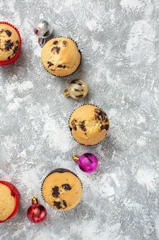 Vista verticale dello spazio vuoto tra deliziosi piccoli cupcakes appena sfornati e accessori decorativi sulla superficie del ghiaccio